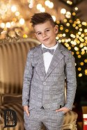 Sports an elegant suit with a black bow tie, plaid